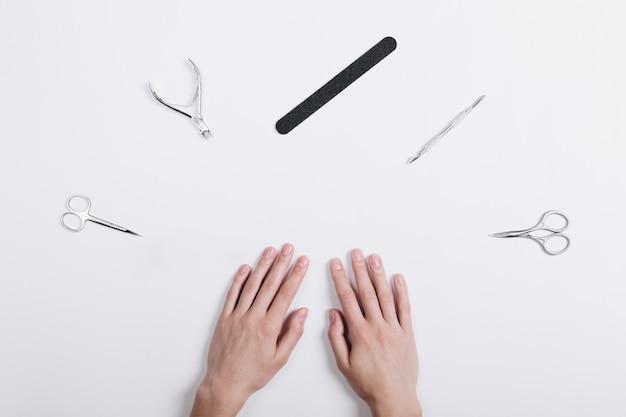 Accessoires voor manicure liggen rond een vrouwelijke handen op een witte tafel