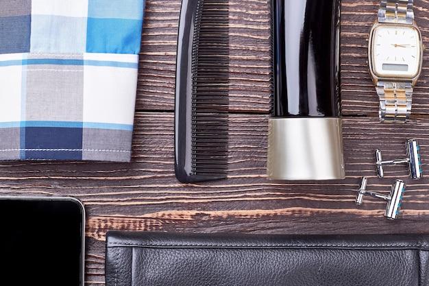 Accessoires voor mannen op hout. keulen, horloge en manchetknopen. kunst van stijlvol zijn.