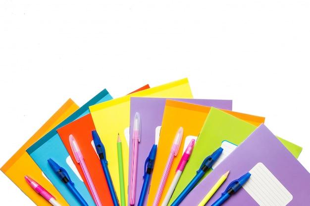 Accessoires voor school, notebooks, pennen, potloden voor de werkplek van een schooljongen op een blauwe achtergrond