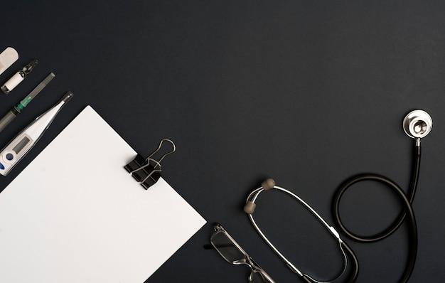 Accessoires voor stethoscoopgeneeskunde met notitieblok, bril en zilveren pen