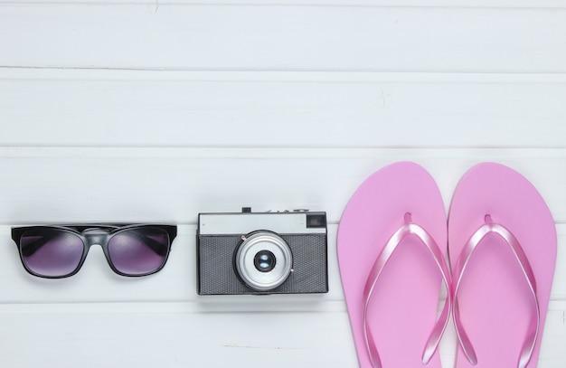 Accessoires voor toerisme op het strand. strandvakantie. flip flops, retro camera, zonnebril op witte houten vloer.