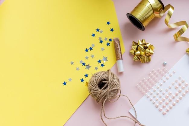 Accessoires voor vakanties. stijlvol papier, schaar, draad op kleurrijke tafel, kopie ruimte. seizoenen