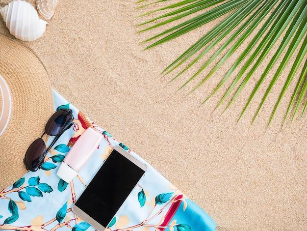 Accessoires zomervakantie concept met bril en hoed op zand strand achtergrond.