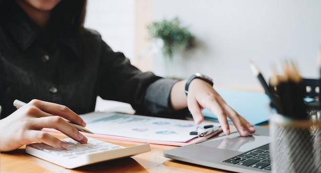 Accountant analyseert en bespreekt de situatie op het financiële verslag met calculator