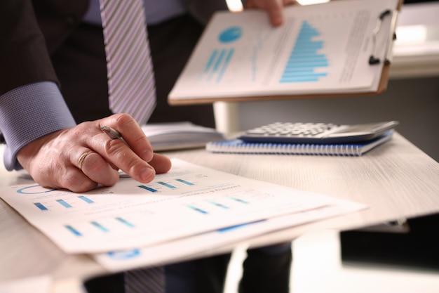 Accountant berekent belastingfactuur met behulp van de rekenmachine