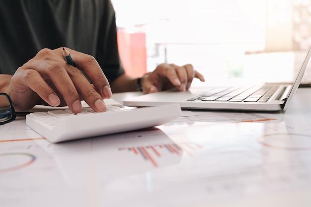 Accountant die aan calculator werken om financieel rapport, boekhoudingsdocument en computer op kantoor, bedrijfs financieel concept te berekenen