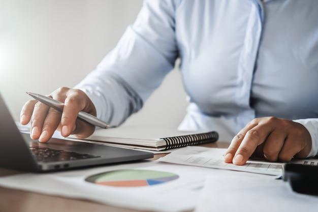Accountant die in bureau werkt dat computerlaptop op bureau met behulp van. financiën en boekhoudkundige concept