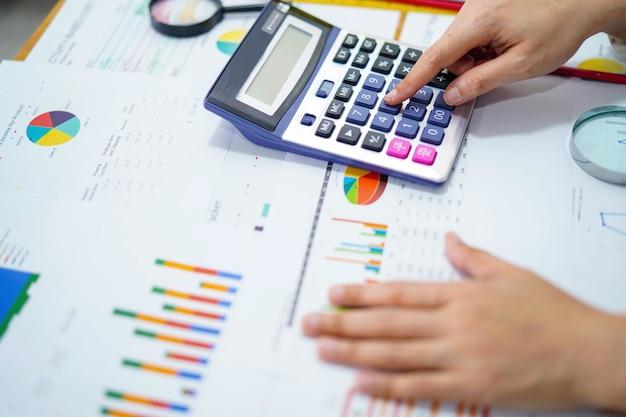 Accountant die met grafiek op kantoor werkt