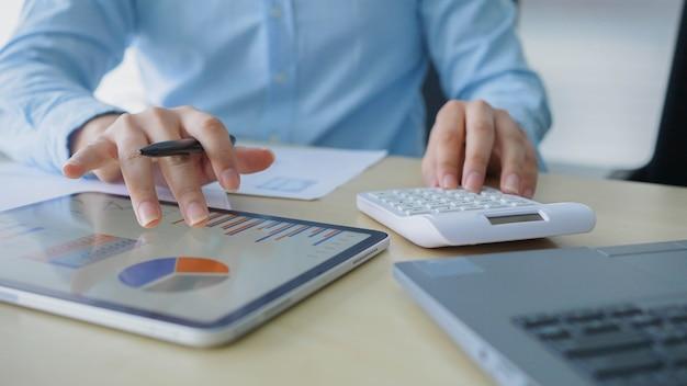Accountant man gebruik berekenen op rekenmachine om samen te vatten of te overwegen op statistisch rapport op kantoor