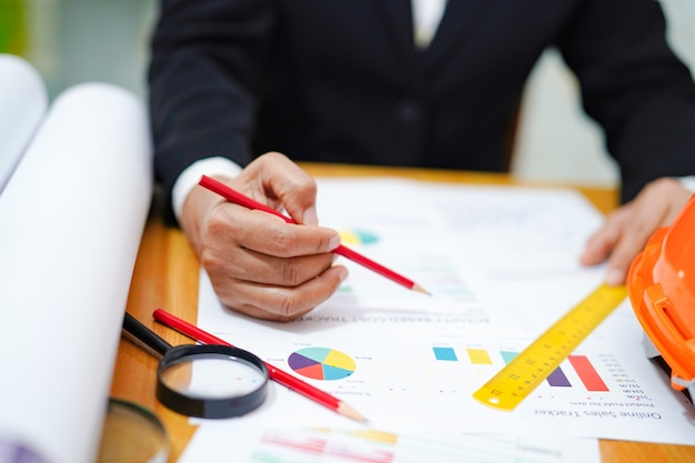 Accountant werkend projectboekhouding met grafiek in modern bureau.