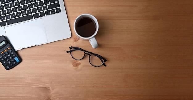 Accountant werkplek met rekenmachine, notebook, bril, koffiekopje, laptop en pen op houten achtergrond.