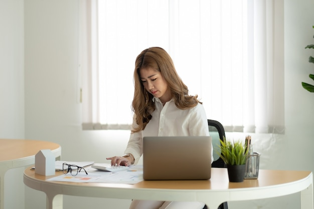 Accountant werkt aan bureau met rekenmachine en laptopcomputer voor het berekenen van het financiële rapport op kantoor met papierwerk.