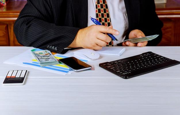 Accountantzakenman tellend geld die nota's maken bij rapport die financiën doen