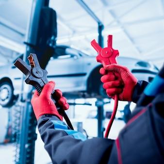 Accumulator opladen. handen en terminals. auto reparatie.