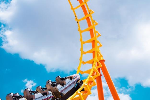 Achtbaan hoog in de zomerhemel in het meest opgewonden, leuke en vrolijke speeltoestel van het themapark