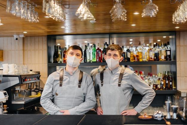 Achter de bar staan twee stijlvolle barmannen in maskers en uniformen tijdens de pandemie. het werk van restaurants en cafés tijdens de pandemie.