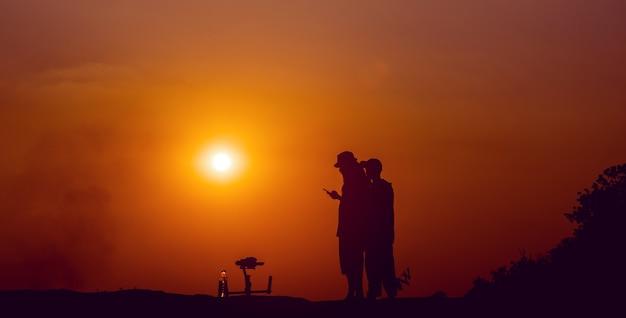 Achter de schermen. het team filmde de filmscène buiten bij zonsondergang. concept silhouet. werk van de videograaf. het filmen van de mv.