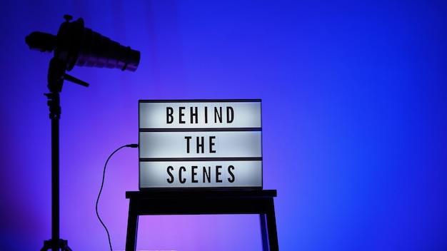 Achter de schermen letterbordtekst op lightbox of cinema lightbox. meerkleurige led. flitskap op statief. videoproductiestudio. achter de schermen lightbox
