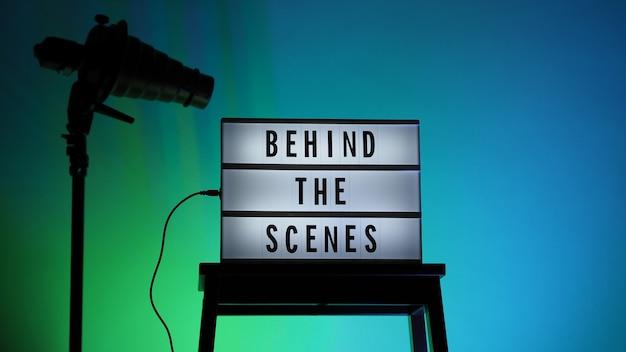 Achter de schermen letterbordtekst op lightbox of cinema lightbox. meerkleurige led. sillhouette flitskap op statief. videoproductiestudio. achter de schermen lightbox