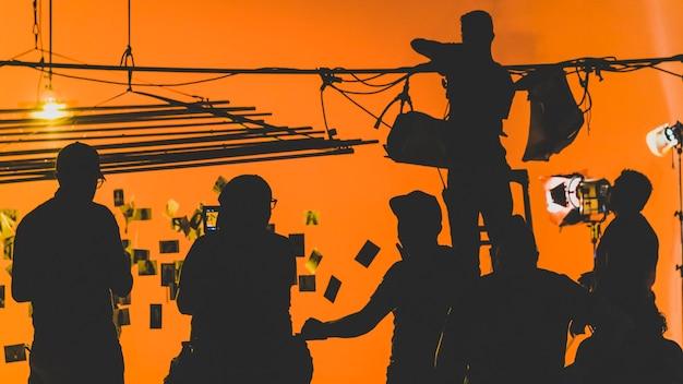 Achter de schermen met cameraman die een videofilm filmt terwijl het productieteam het podium opzet
