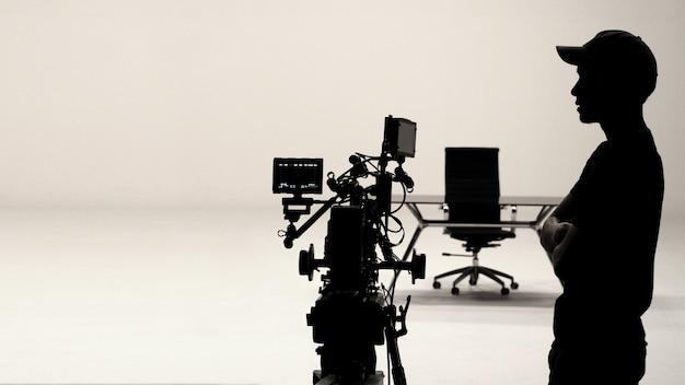 Achter de schermen of making of film in de studio en silhouet van cameraman.