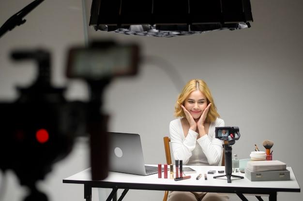 Achter de schermen presenteert jonge blonde vrouwelijke ondernemer die met laptop werkt cosmetische producten tijdens online livestream op wit