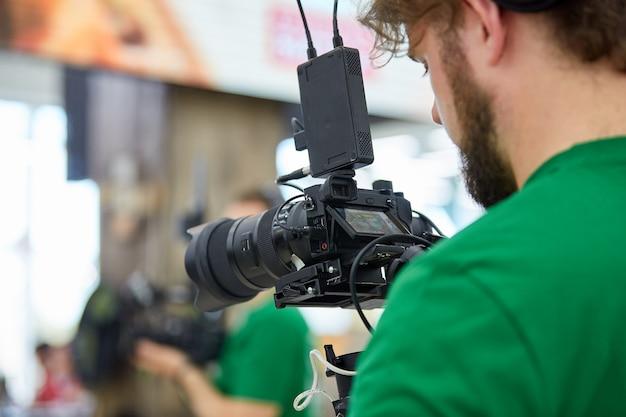 Achter de schermen van filmopnames of videoproductie en filmploegenteam met camera-apparatuur op buitenlocatie.