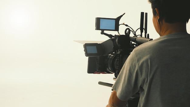 Achter de schermen van videoproductie in de grote studio met professionele apparatuur zoals camerastatief en kraan.