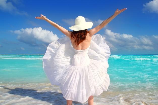 Achter de vrouwenwind die van het strand witte kleding schudt