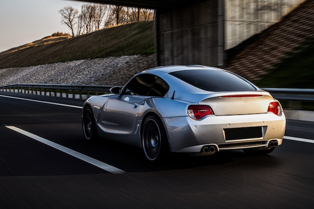 Achter- en zijaanzicht van een metallic zilveren coupe op de weg.