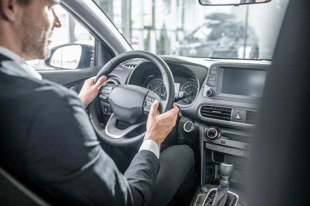 Achter het stuur. jonge man in elegant pak zit met stuur in nieuwe auto en kijkt naar donker dashboard in prachtig interieur