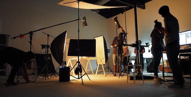 Achter het team van de opnameploeg en het silhouet van camera en apparatuur in de studio.