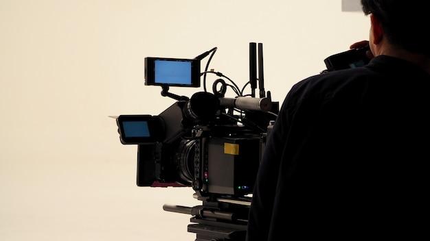 Achter het video-opnameteam van de productieploeg werkt en een set full hd-camera-apparatuur in de studio