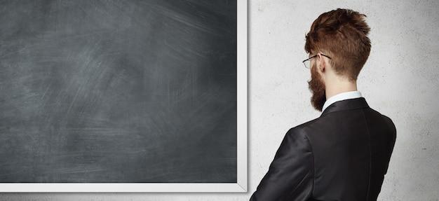 Achter mening die van jonge werknemer formeel kostuum en bril draagt, die zich voor bord bevindt, iets voorstelt.