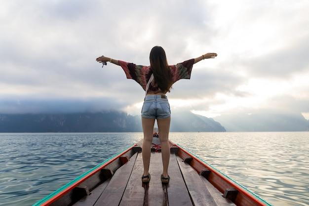 Achter mening van aziatische jonge vrouw die door houten boot bij zonsopgang tussen het eiland khao sok thailand reist