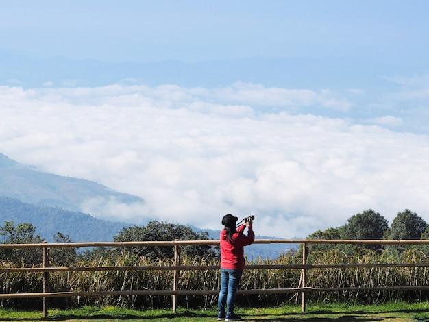 Achter mening van de aziatische camera die van de vrouwenholding foto de mist over hoge berg in chiangmai nemen