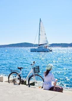 Achter mening van de zitting van de toeristenvrouw bij fiets op verharde stoep onder duidelijke blauwe hemel lettend op varend schip in azuurblauw zeewater