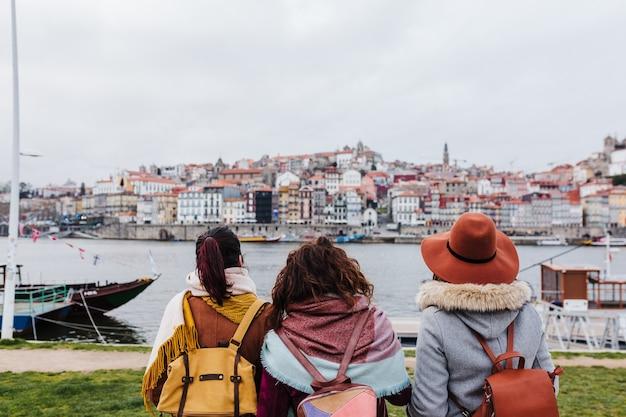Achter mening van drie vrouwen die uitzicht op porto bezoeken door de rivier. reis- en vriendschapsconcept