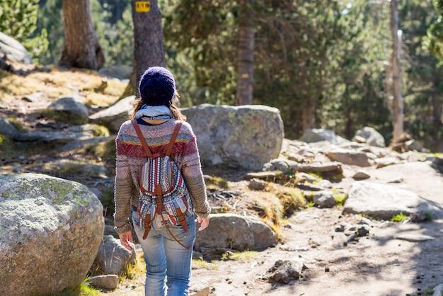 Achter mening van een backpackervrouw die een wollen glb wandelen draagt