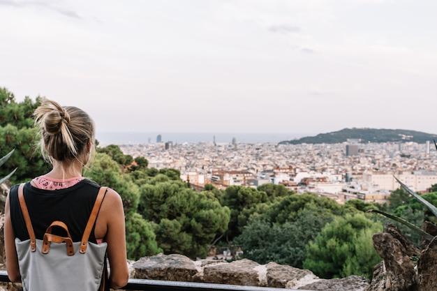 Achter mening van een blonde vrouw die de stadsmening van barcelona bekijkt