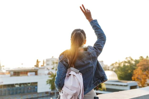 Achter mening van een jonge vrouw die jas draagt die buiten loopt bij de stadsstraat