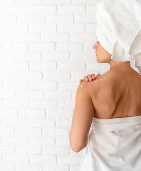 Achter mening van een jonge vrouw die room op haar schouders toepast