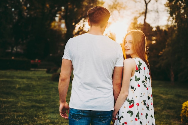 Achter mening van een kaukasisch paar dat buiten tegen zonsondergang dateert terwijl het meisje met rood haar terug kijkt naar camera glimlachend hand in hand.
