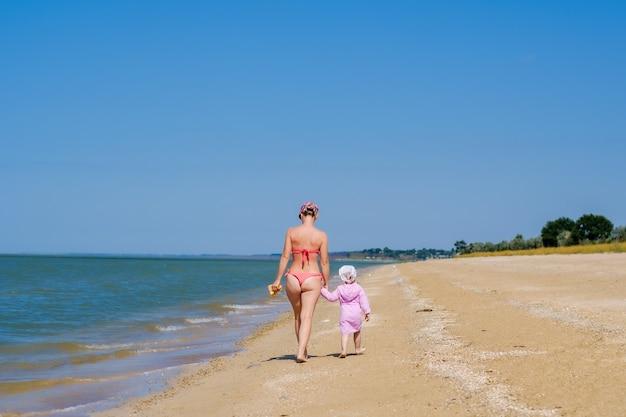 Achter mening van een moeder en een babymeisje die langs een verlaten zandig overzees strand langs de branding tegen een blauwe wolkenloze hemel lopen. een vrouw en een kind houden elkaars hand vast. zonnige dag. familie vakantie concept