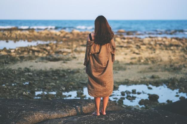 Achter mening van een mooie aziatische vrouw die zich alleen op het strand aan de kust bevindt