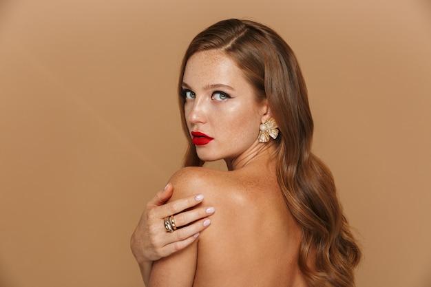 Achter mening van een mooie jonge vrouw die make-up en juwelentoebehoren draagt poseren geïsoleerd over beige muur