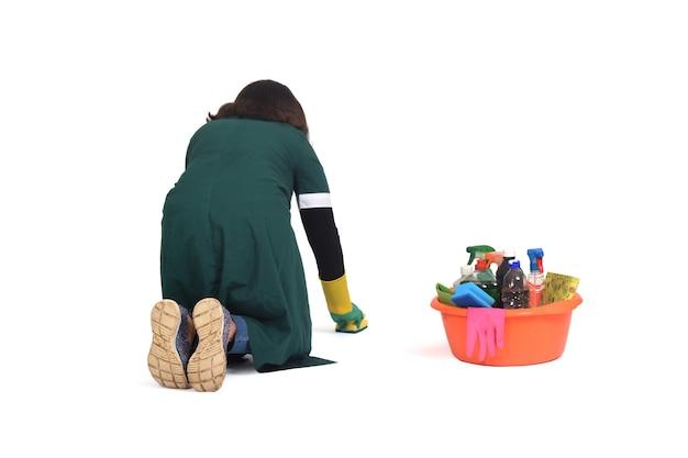 Achter mening van een vrouw die de vloer schrobt op haar die knieën op wit wordt geïsoleerd