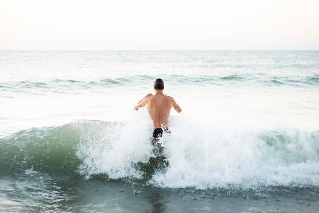 Achter mening van mannelijke zwemmer die in de oceaan krijgt