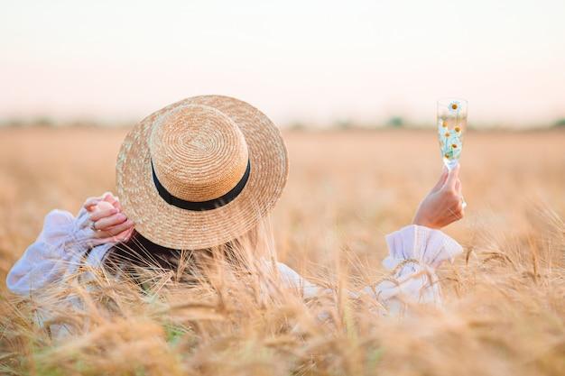 Achter mening van meisje in een tarweveld. mooie vrouw in jurk in een strooien hoed met rijpe tarwe in handen