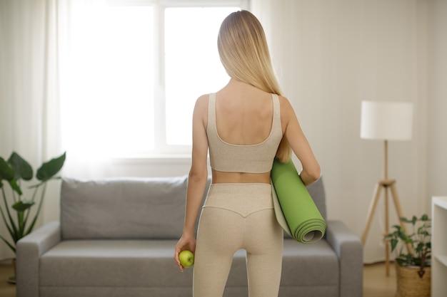 Achter mening van van gezonde slanke jonge vrouw die een appel en yogamat houdt, die thuis staat. gezond